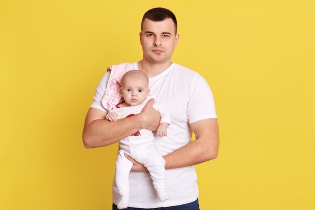 黄色の壁に孤立したポーズをしながら、生まれたばかりの赤ちゃんの息子または娘を保持している