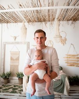 Father holding newborn medium shot