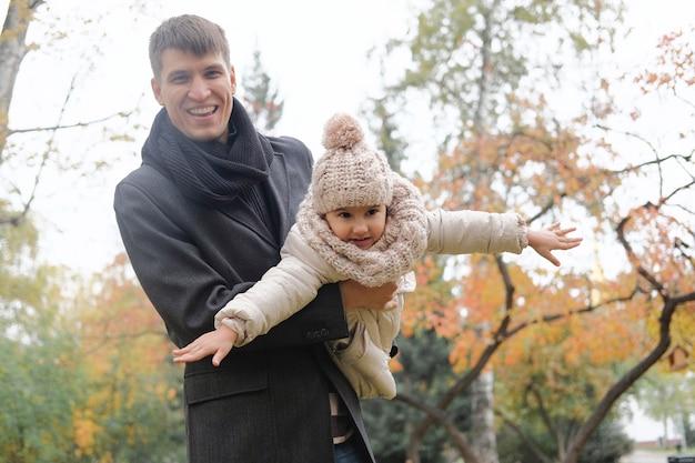 Отец держит дочь на руках и показывает летающий самолет.