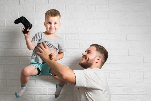 Father holding son in air at home