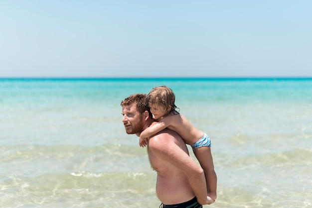 Father holding son at the beach