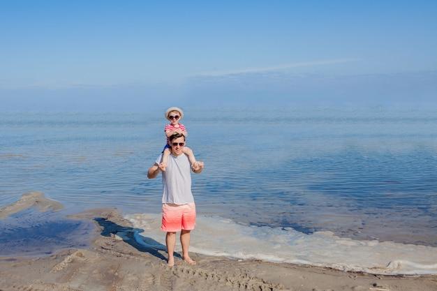 Отец держит сына на плечах на пляже.