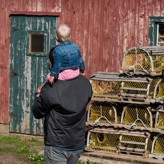 Отец, держащий малыша на плече в рыболовном сарае, северный рустико, остров принца эдуарда, канада