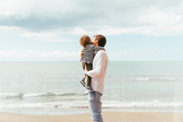 Отец держит малыша сына на берегу моря