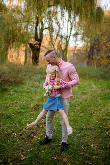 Отец держит дочь на руках.