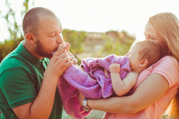 Father holds feet of his child enveloped in violet towel