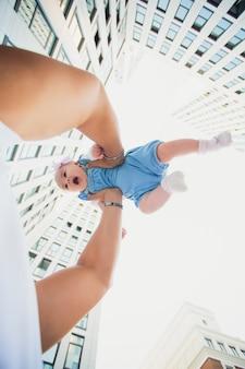 Отец держит свою дочь на фоне небоскребов. стеклянные здания. ребенок на фоне неба