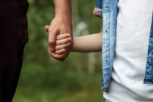 Father holds his little son by the hand.