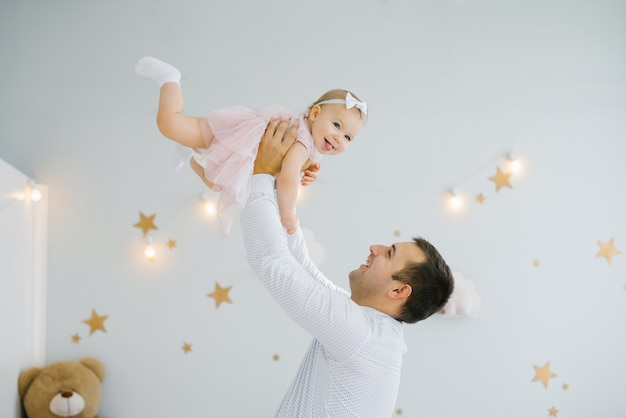 The father holds the one-year-old daughter in a pink dress on high arms, the daughter smiles and is happy.