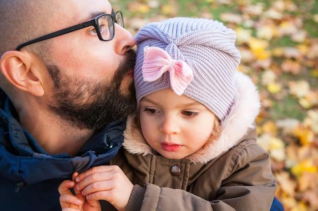 父は秋の屋外で彼のかわいい小さな娘を抱きしめてキスします