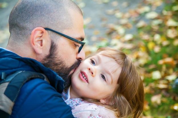 아버지 포옹과 야외에서 그의 귀여운 작은 딸 키스 프리미엄 사진