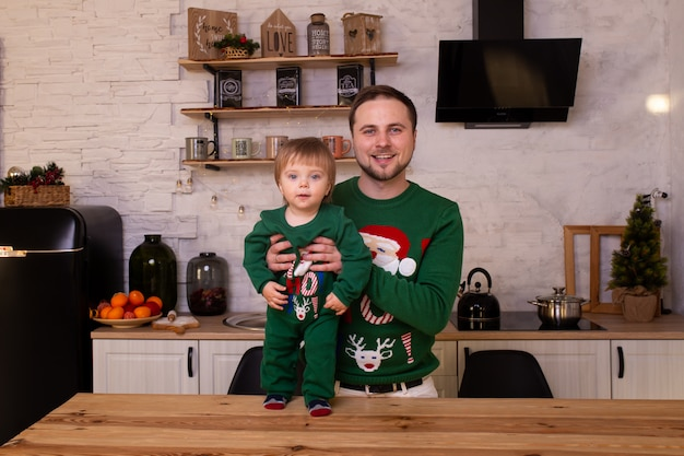 Father hugging her child in christmas kitchen at home.