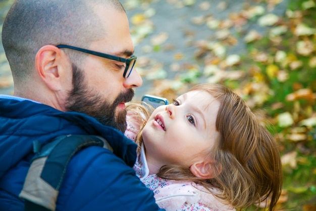 야외에서 그의 귀여운 작은 딸을 안고있는 아버지