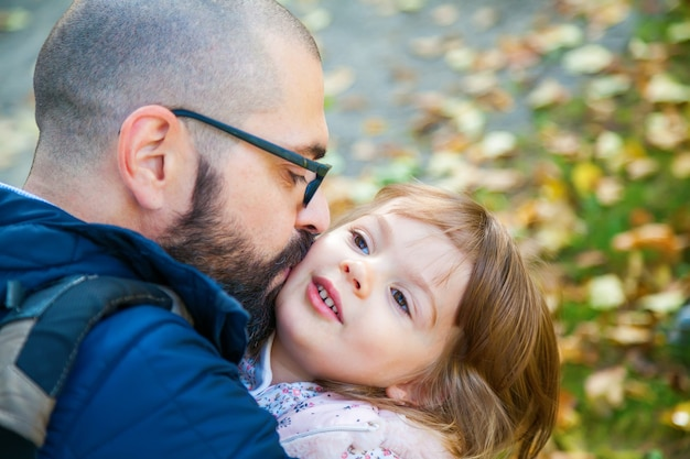 Father hugging and kissing his cute little daughter outdoors