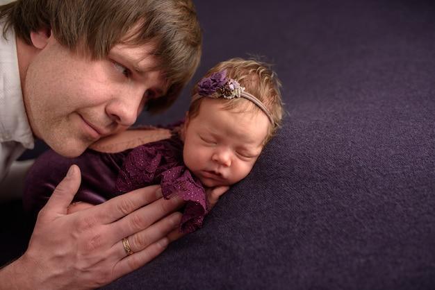 Отец обнимает свою новорожденную дочь.