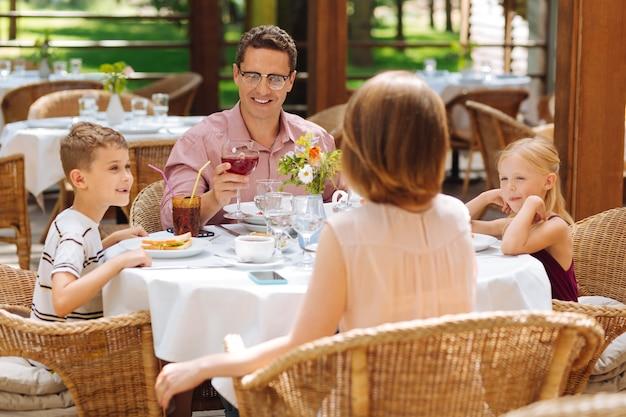 Отец в очках. темноволосый отец в очках с бокалом вина поздравляет жену с повышением в должности
