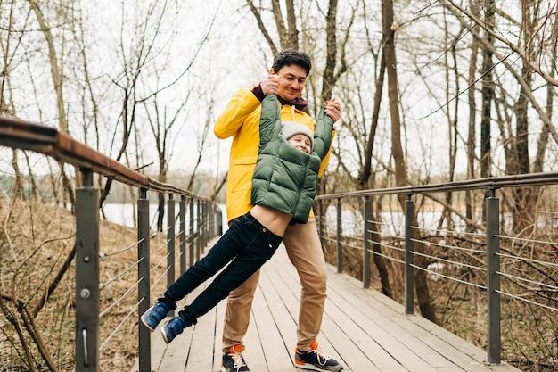 Отец в желтом плаще и сын, весело проводящий время в лесу, счастливая семья с ребенком, мальчиком, играющим и