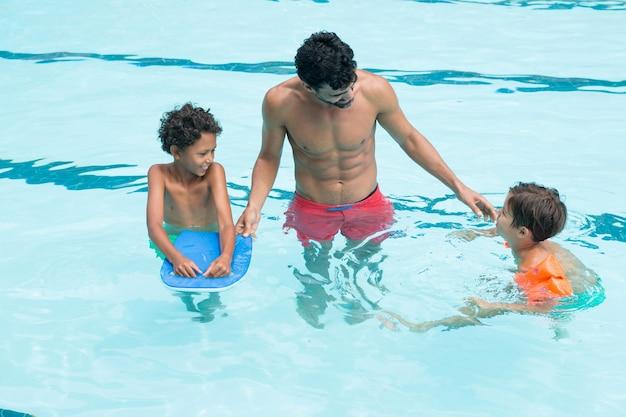 Отец взаимодействует с детьми в бассейне в развлекательном центре
