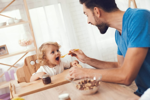 Father is feeding his son a breakfast.