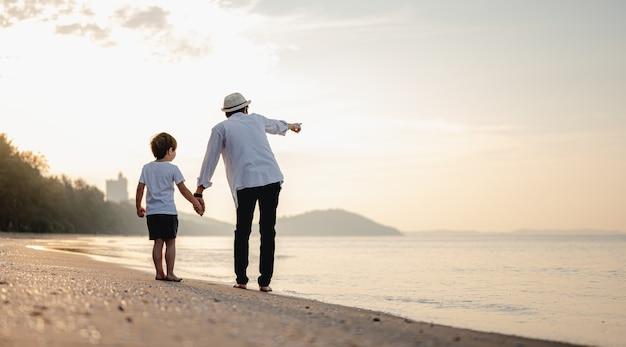 父は休日の休日の家族の日没時に子供と手をつないでビーチを歩いています