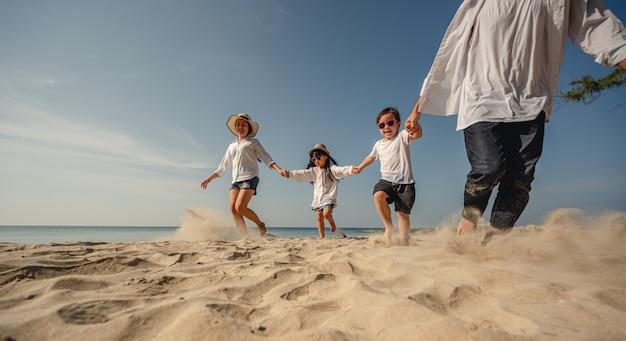 父はビーチで休日の家族の休日に子供と手をつないで砂の上を歩いています
