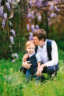 Отец целует своего мальчика в макушку с цветущей вистерией