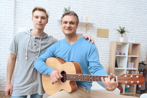 Father is playing on guitar and his son listening