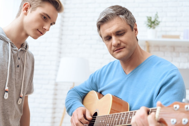 Father is playing on guitar and his son
