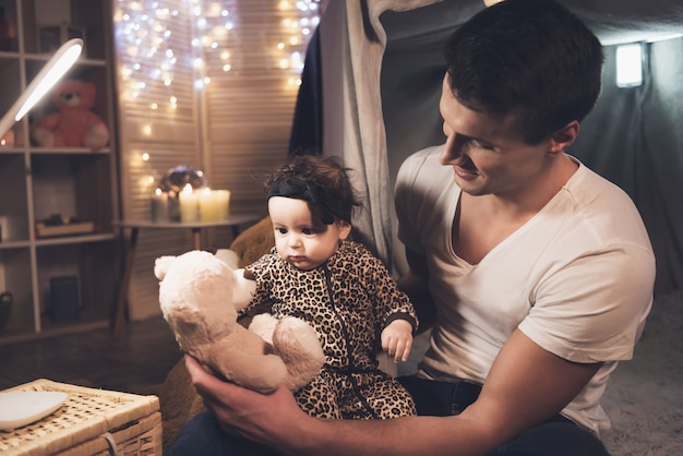 Father is playing with little baby daughter in blanket