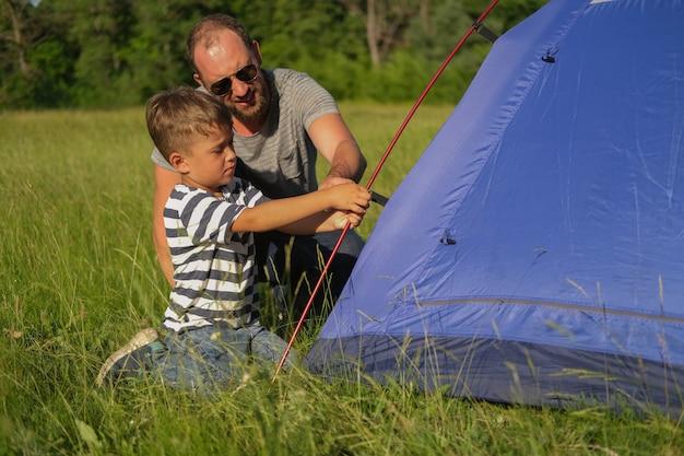 Отец учит сына ставить палатку. семейный поход. счастливая семья. фото высокого качества