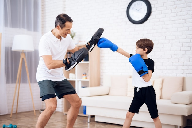 The father is training his son boxing.
