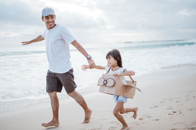 Father and kid running with toy cardboard airplane at the beach