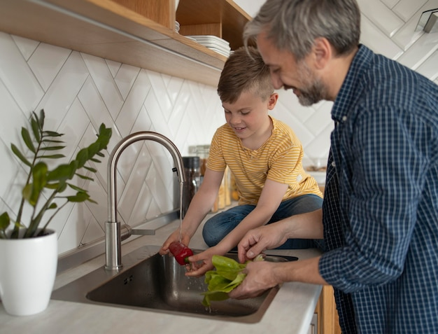 Padre e figlio che lavano le verdure