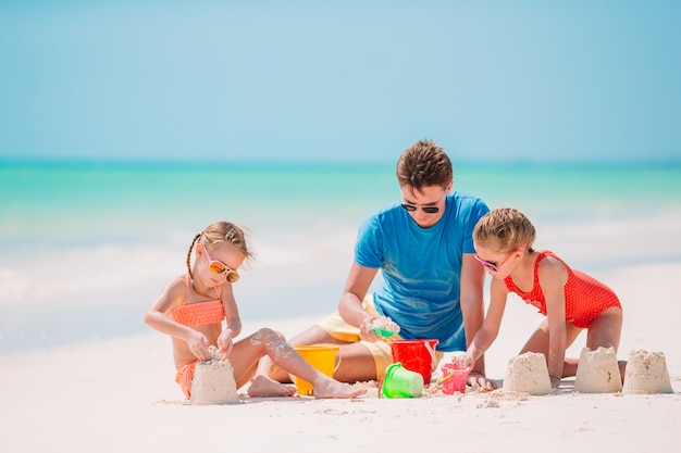 Father and kids making sand castle at tropical beach. family ...