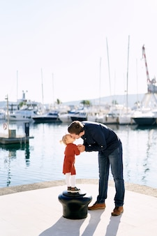 Father kissing his daughter on a boat pier in montenegro.