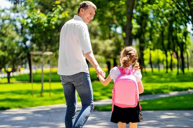 Отец ведет дочь в школу в первом классе
