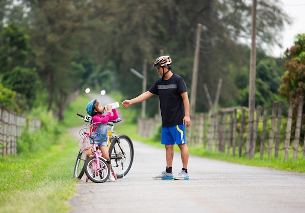 Father let his daughter drink water while cycling in the park