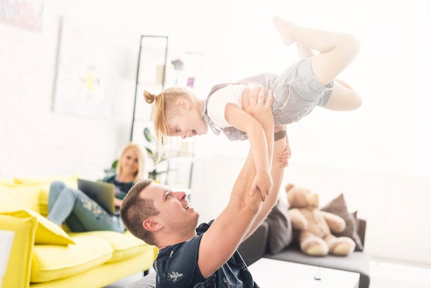 Father lifting her happy daughter at home