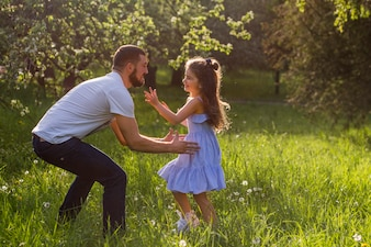 Father lifting his daughter in park
