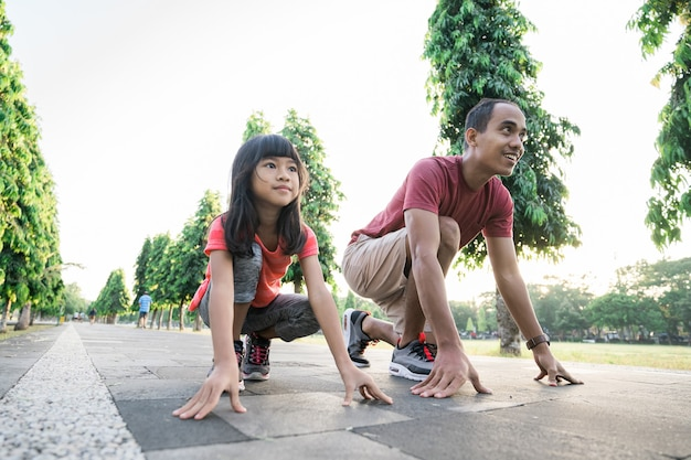 Father and little daughter do exercises in outdoor healthy lifestyle of family with child