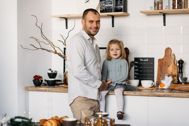 Father and little daughter in kitchen at home.