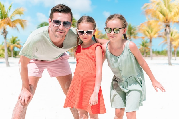 Father and little girls have a lot of fun on white sandy beach