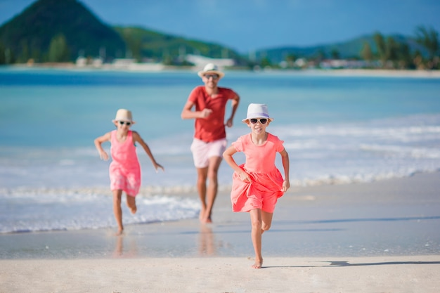 Father and little kids enjoying beach summer tropical vacation