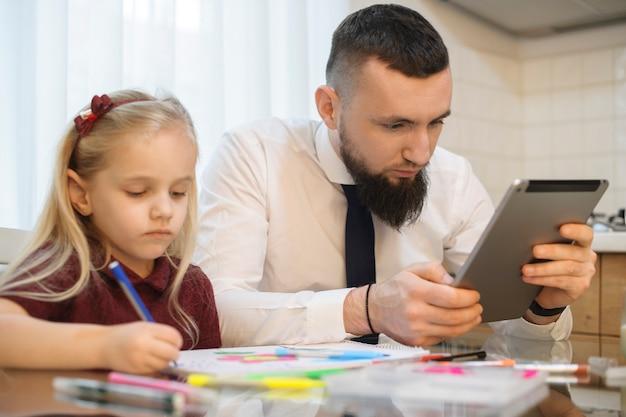 Отец смотрит на экран планшета на кухне перед тем, как пойти на работу, пока его маленькая девочка рисует.