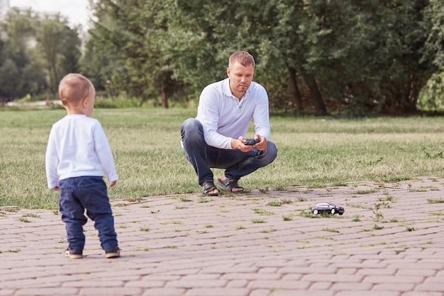 Отец смотрит на своего маленького сына во время прогулки в парке