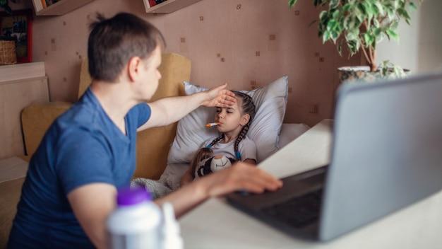 ノートパソコンの画面を見て、自宅でオンラインで医師と相談する父親
