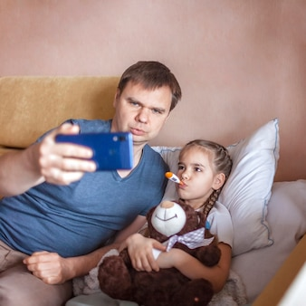 父親がスマートフォンの画面を見て、自宅でオンラインで医師に相談する