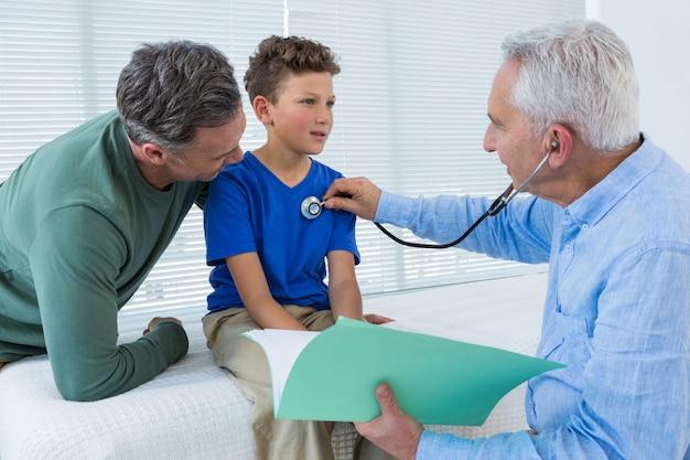 Отец смотрит на сына во время осмотра врачом
