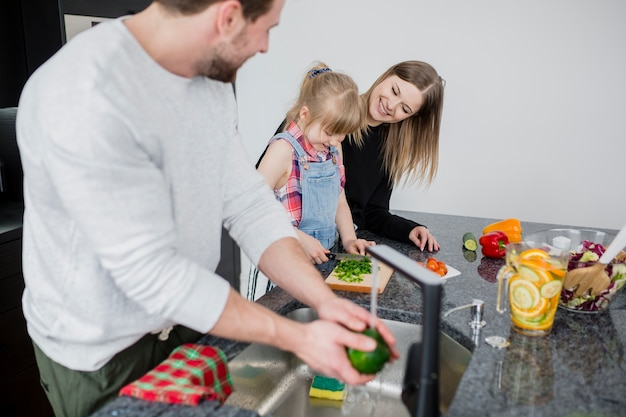 Father looking at daughter and wife cutting vegetables Free Photo