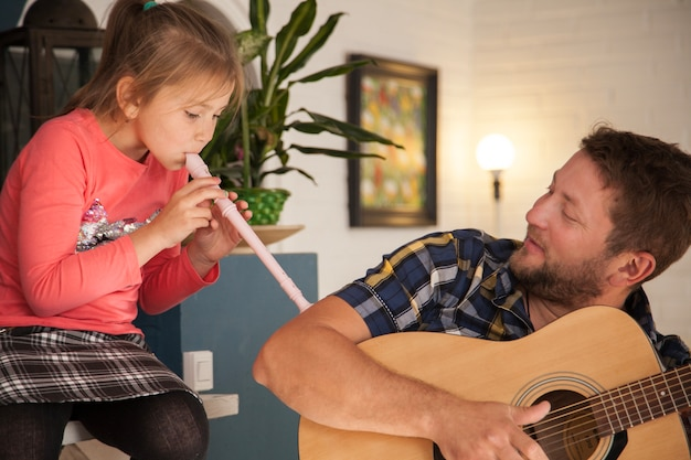 Father looking at his daughter while playing the flute
